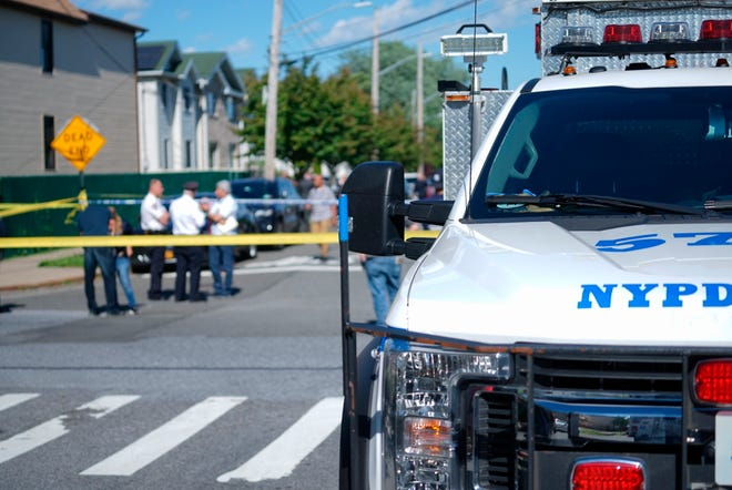 New York City Police officials gather along Wilcox Street behind the 121st Precinct station house following a report of a police officer shot in the Staten Island borough of New York, Friday, June 14, 2019. The officer's condition wasn't immediately known. (Joseph Ostapiuk/Staten Island Advance via AP)