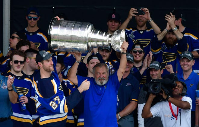 Former Blues great Bob Plager lifts the Cup.