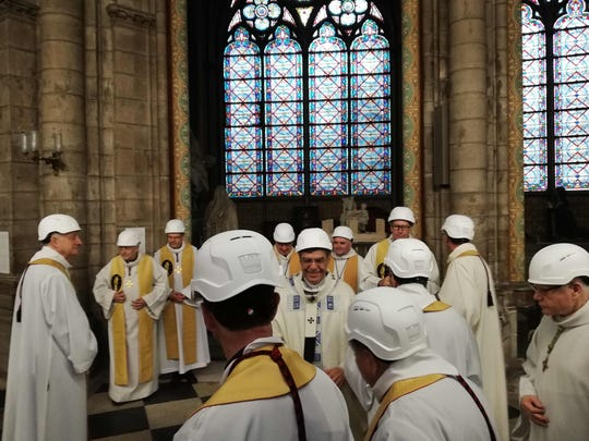 The Archbishop of Paris Michel Aupetit (C) greets other members of the clergy following the first mass in a side chapel, two months to the day after a devastating fire engulfed the Notre-Dame de Paris cathedral.