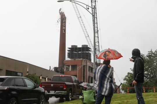 People watch as the Hudepohl smokestack is taken down with a wrecking ball on Sunday June 16, 2019.