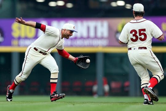 Cincinnati Reds first baseman Joey Votto (19) flips the ball to first Cincinnati Reds starting pitcher Tanner Roark (35) for an out in the third inning of an MLB baseball game against the Texas Rangers, Saturday, June 15, 2019, at Great American Ball Park in Cincinnati.