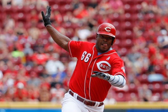 Cincinnati Reds' Yasiel Puig runs to third on a single by Josh VanMeter off Texas Rangers relief pitcher Ariel Jurado in the second inning of a baseball game, Sunday, June 16, 2019, in Cincinnati.