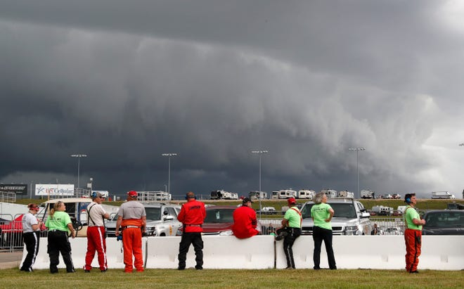 Track workers watch storm clouds move in over the track before Saturday's scheduled M&M's 200 at Iowa Speedway.