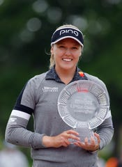 Brooke Henderson holds the championship trophy after winning the Meijer LPA Classic golf tournament Sunday in Grand Rapids.