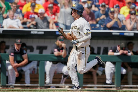 Michigan's Jesse Franklin pumps his fist as he runs past the Texas Tech dugout to score on a throwing error in the seventh inning Saturday.