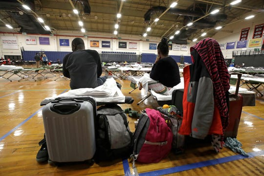 In this June 13, 2019 photo, a migrant couple sit with their belongings inside the Portland Exposition Building in Portland, Maine.