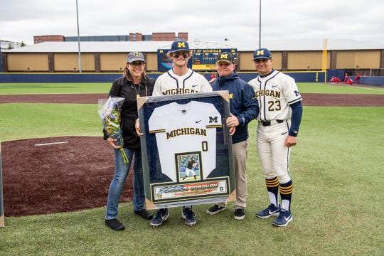 Erik Bakich presents Joe Donovan and his parents with a framed jersey to honor Charlie Donovan on Senior Night.