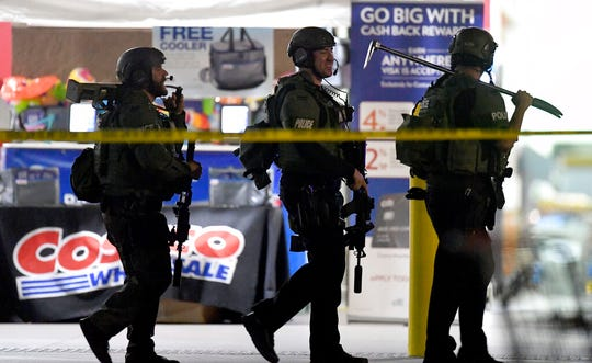 Heavily armed police officers exit the Costco following a shooting inside the wholesale warehouse in Corona, Calif.,  Friday, June 14, 2019.