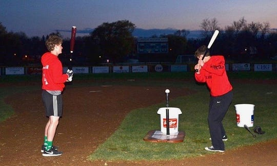 Joe, left, and Charlie Donovan get in some night-time batting practice.