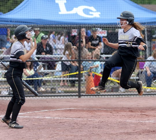 Laura Bennett jumps in the air and is greeted by Emily VanDelinder after scoring a run against Cicero-North Syracuse in the Class AA softball state final June 15, 2019 at Moreau Recreational Park in South Glens Falls.