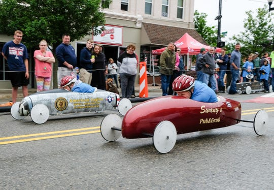 Cy Huneycutt, 15, left, and Abby Thelen, 13, race in the Super Stock Division in the Soap Box Derby in St. Johns Sunday, June 16, 2019.