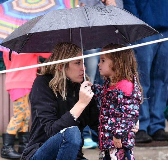 Two people take refuge under an umbrella while watching a Soap Box Derby in downtown St. Johns on a rainy Sunday, June 16, 2019.