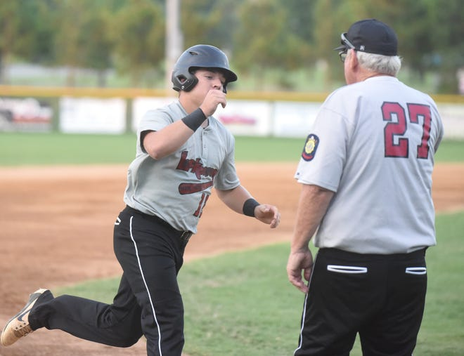 Lockeroom's Caleb Johnson is congratulated by coach Lester White as he rounds third base on a home run.
