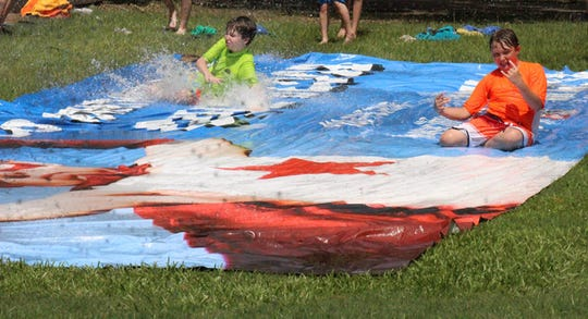 Kids cool down on a water slide during summer camp at the Montgomery Zoo.