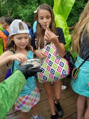 Campers get treats to feed the otters during summer camp at the Montgomery Zoo.