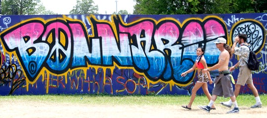 Music fans walk past artwork and graffiti at the campground at Bonnaroo Music and Arts Festival on on June 16.