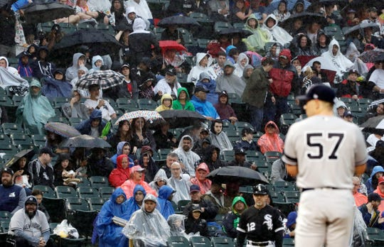 As rain falls, fans watch a baseball game between the New York Yankees and the Chicago White Sox during the second inning in Chicago, Saturday, June 15, 2019.