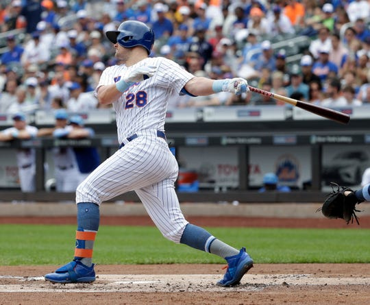 New York Mets' J.D. Davis hits an RBI single during the first inning of a baseball game against the St. Louis Cardinals at Citi Field, Sunday, June 16, 2019, in New York. (AP Photo/Seth Wenig)