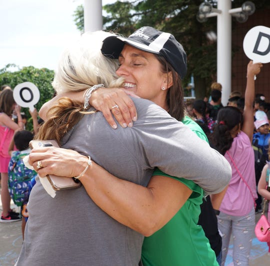 Principal Jennifer Michos gets a hug from a friend on her last day leading Novi's Parkview Elementary.