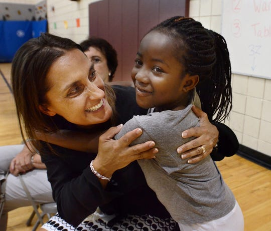 "With a hug and a smile, Parkview Elementary School student Audra Sexsmith welcomes back Principal Jennifer Michos to the school on June 10, 2016. Michos has been on a leave for a health issue for the last two months - but she promised to be back at the school on Eleven Mile Road next fall ""at one hundred percent"". Michos took time that day to thank the staff, students and parents of Parkview who kept her on the road to health with care packages, flowers, and gift baskets every week she was away from school."