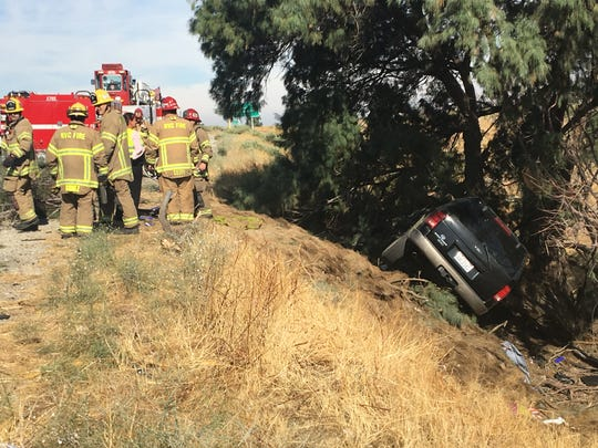 Cal Fire firefighters gather near an embankment near a Ford Explorer damaged in a crash on westbound Interstate 10 on June 16. Its driver was a Brawley woman who died at the scene, investigators say. Two others were injured.