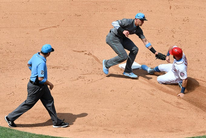 Jun 16, 2019; Washington, DC, USA; Arizona Diamondbacks shortstop Nick Ahmed (13) tags out Washington Nationals right fielder Adam Eaton (2) attempting to steal during the fourth inning at Nationals Park. Mandatory Credit: Brad Mills-USA TODAY Sports