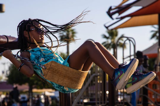 Nia Martin, 9, swings on the playset at the Juneteenth Festival held at Eastlake Park in Phoenix on June 15, 2019.