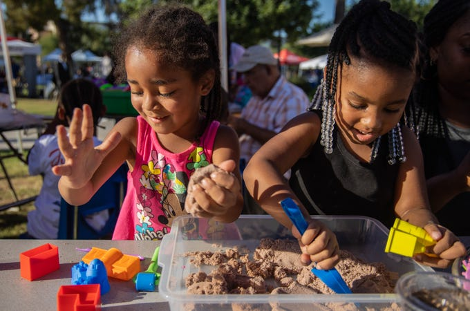 Cynthia Vincent, 4, (left) and Kailee Vincent, 4, (right) play at one of the craft stations set up for kids at the Juneteenth Festival held at Eastlake Park in Phoenix on June 15, 2019.