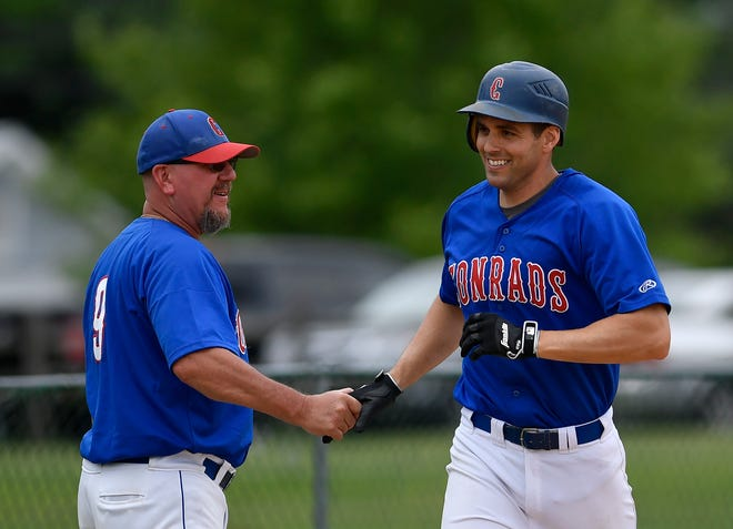 Conrads coach Chad Kennell, left, congratulates Rick Thompson on his solo homerun against Windsor, Sunday, June 16, 2019.John A. Pavoncello photo
