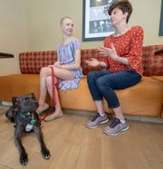 Sarah Pennington, left, listens to her mother Michelle Pennington talk while her service dog Daisy sits at her feet.
