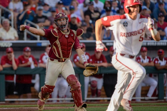 Jun 15, 2019; Omaha, NE, USA; Florida State Seminoles catcher Matheu Nelson (63) throws out Arkansas Razorbacks third baseman Jacob Nesbit (5) on a dropped third strike in the 2019 College World Series at TD Ameritrade Park. Mandatory Credit: Steven Branscombe-USA TODAY Sports