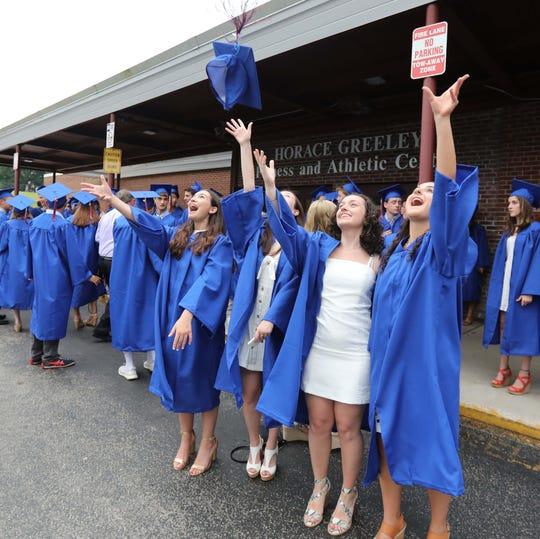 Graduates practice tossing their caps before graduation ceremonies at Horace Greeley High School in Chappaqua June 16, 2019.