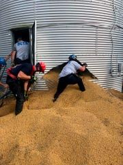 In this May 30, 2019 photo provided by the Ross Township Fire Department rescue personnel shovel soybeans out of the bottom of a bin during an effort to rescue farmer Jay Butterfield, who was buried up to his neck inside. He became buried up to his neck while trying to break up clumps of soybeans in the bin on his farm in Ross Township, Ohio.