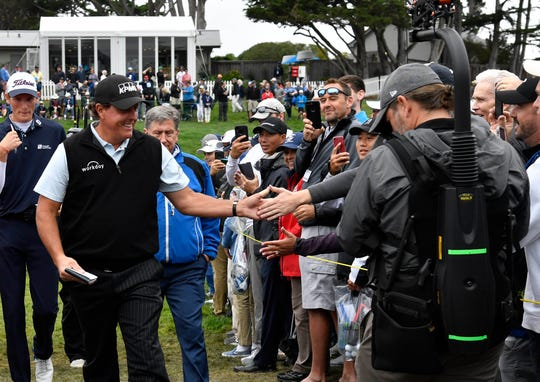 Phil Mickelson greets fans as he walks to the fouth tee during the third round.