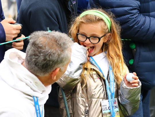 Layla Friedman reacts with father Gary Friedman after getting a ball from Brooks Koepka on the second hole.