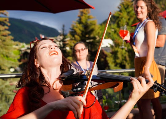 Violinist Jessica Borth plays as the sun sets during a rooftop Venetian spritz party during the 2019 Food & Wine Classic in Aspen.