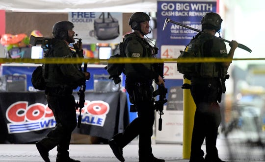 Police officers exit a Costco after a shooting inside the wholesale warehouse Friday in Corona, Calif.