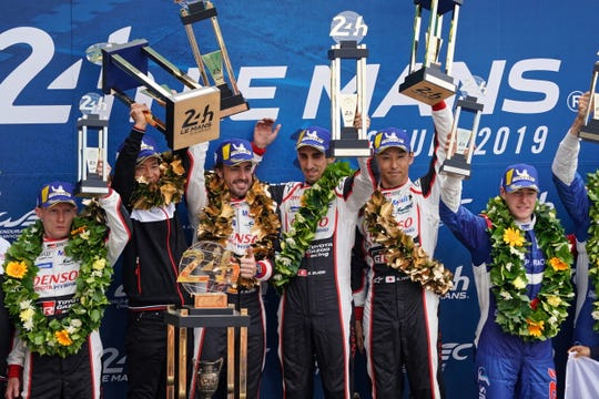 Sebastien Buemi, Kazuki Nakajima and Fernando Alonso celebrate on the podium after winning the 2019 24 Hours of Le Mans.