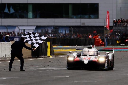Kazuki Nakajima takes the checkered flag in his Toyota Gazoo Racing TS050 Hybrid.