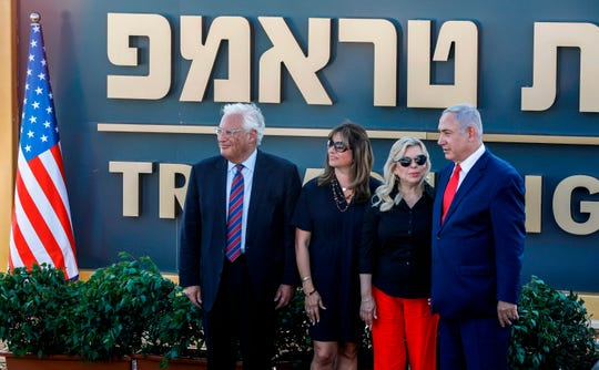 "(L to R) US Ambassador to Israel David Friedman, his wife Tami, Sara Netanyahu, and her husband Israeli Prime Minister Benjamin Netanyahu pose for a picture before the newly-unveiled sign for the new settlement of ""Ramat Trump"", or ""Trump Heights"" in English, named after the incumbent US President during an official ceremony in the Israeli-annexed Golan Heights on June 16, 2019."