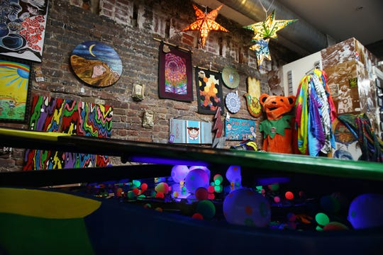 Melinda Murat-Blevins, co-owner of Type B Tie Dye Asbury Park, displays her hand-painted baby grand piano, decorated with black lights inside, and some of her tie dye items at the Type B Tie Dye location in Asbury Park, NJ Monday June 17, 2019.