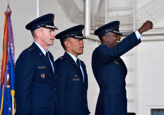 """Col. Brandon Parker raises a fist to cheer while he and Col. Jose """"Ed"""" Sumangil and Maj. Gen. James Dawkins Jr. sing """"Wild Blue Yonder,"""" the U.S. Air Force's official song at the end of Monday's 7th Bomb Wing change of command."""