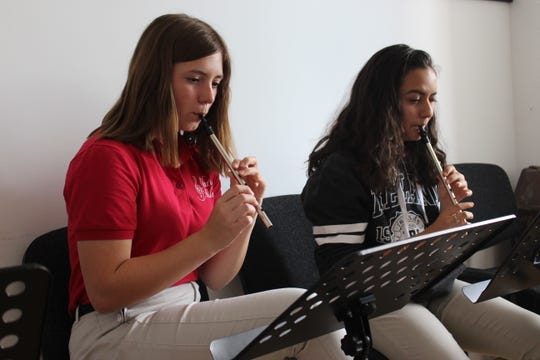 Singers Caroline Statler and Gabby Trujillo learning the Irish tin whistle.