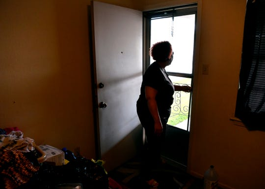 Deborah Battee looks out her back door into the carport June 12. The EF-2 tornado May 18 had flung a neighbor's roof under her car. Battee's car was totaled and her home damaged.