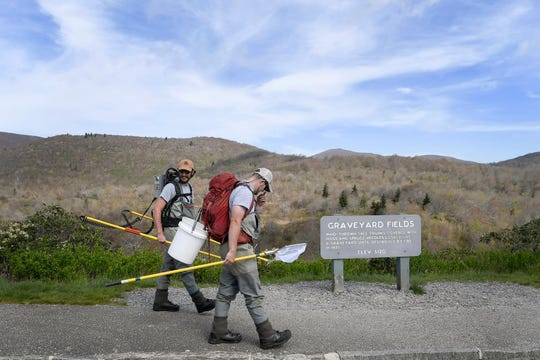 Conservation technicians Kenneth Lingerfelt, left, and Justin Nichols walk toward the trailhead to Yellowstone Prong in the Pisgah National Forest May 1, 2019.