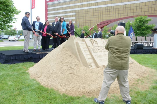 Tribal Council members pose for photos near a sand sculpture built for the groundbreaking.
