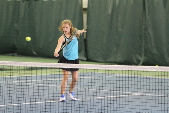 Anna Sobol sends the ball over the net at Creekside Racquet Club on June 12, as she prepares to return to the tennis court at Owen High School this fall.