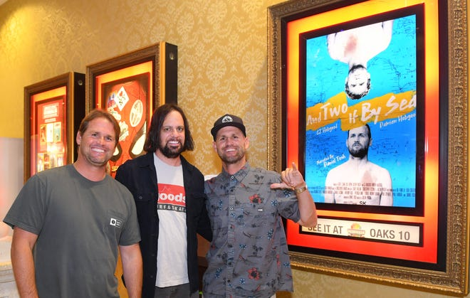 """CJ Hobgood, director Justin Purser, and Damien Hobgood pose next to the poster. The sold-out Brevard premiere of """"And Two If By Sea"""" was held at Premiere Theaters Oaks 10 in Melbourne Sunday night, June 16. The documentary follows the surfing careers of identical twins CJ and Damien Hobgood, of Satellite Beach."""