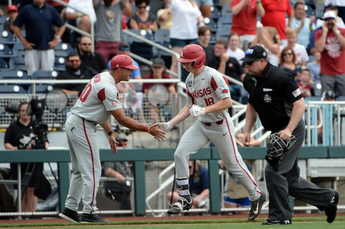 Jun 17, 2019; Omaha, NE, USA; Arkansas Razorbacks outfielder Heston Kjerstad (18) greets coach Nate Thompson after hitting a home run in the second inning against the Texas Tech Red Raiders in the 2019 College World Series at TD Ameritrade Park. Mandatory Credit: Steven Branscombe-USA TODAY Sports