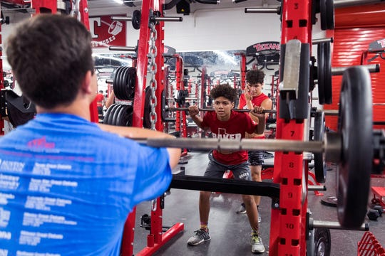 Jaedyn Brown (center), 13, lifts weights while Nathan Ramirez (back), 14, spots him while participating in a strength and conditioning camp at Ray High School on Monday, June 17, 2019. The students rotate between a section focused on cardiovascular strength, core strength, and weight lifting.